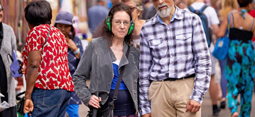 Женщина носит промышленные наушники, чтобы спастись от громких звуков